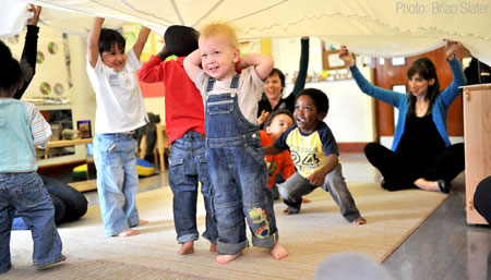 Children playing happily waving a large light-weight sheet.