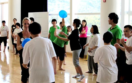 Groups session with participants moving around the room and dancing with balloons